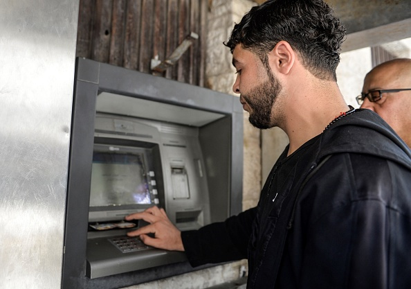 GAZA CITY, GAZA - MAY 10: Palestinians arrive to withdraw their salaries from atm after the decision of about 30-percent pay cut for April by the government officials in Gaza City, Gaza on May 10, 2017.  (Photo by Mustafa Hassona/Anadolu Agency/Getty Images)